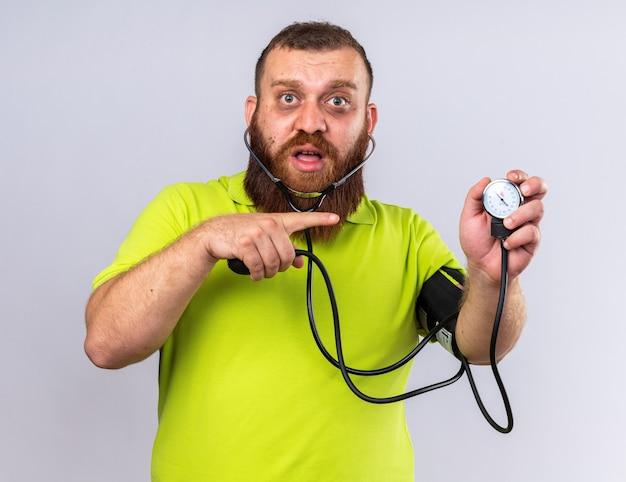 Niezdrowy brodaty mężczyzna w żółtej koszulce polo źle się czuje, mierząc ciśnienie krwi za pomocą tonometru wskazującego palcem wskazującym, patrząc zmartwionego, stojąc nad białą ścianą