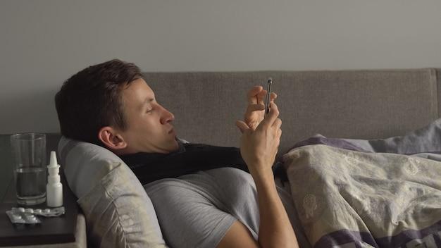 Niezdrowy mężczyzna w łóżku obok swoich leków w domu dzwoniący przez telefon mężczyzna cierpiący na przeziębienie i...