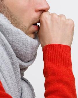 Niezdrowy mężczyzna w pomarańczowym swetrze cierpi na kaszel płucny z powodu przeziębienia, grypy