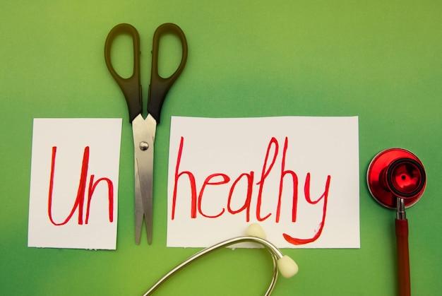 Niezdrowy napis. stetoskop i nożyczki na zielono. ręcznie napisany czerwony napis. medycyna i zdrowie.