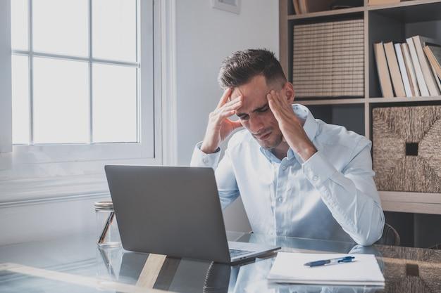 Niezdrowy zestresowany biznesmen zdejmujący okulary, pocierający powieki, cierpiący na zespół suchego oka z powodu długiego przepracowania komputera, masujący mostek głowy uśmierzający ból w biurze w domu.