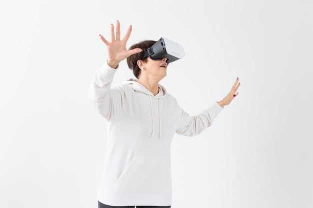 Niezidentyfikowana kobieta w średnim wieku w jasnym swetrze gra w trójwymiarową grę w okularach wirtualnej rzeczywistości