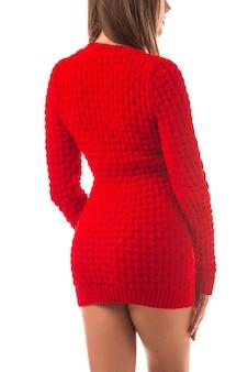 Niezidentyfikowana młoda brunetka kobieta pozuje w stylowej odzieży damskiej w czerwony sweter i beżowe spodnie.