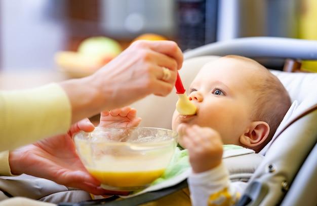 Niezidentyfikowana ręka matki ostrożnie karmi słodką, zdrową nowonarodzoną dziewczynkę pokarmem dla niemowląt