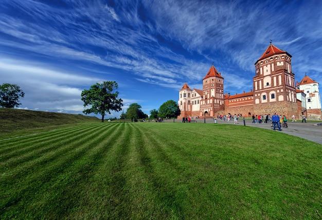 Niezidentyfikowani ludzie chodzą w pobliżu zamku w mirze w obwodzie grodzieńskim na białorusi. zamek jest fortyfikacją obronną xvi-xvii wieku