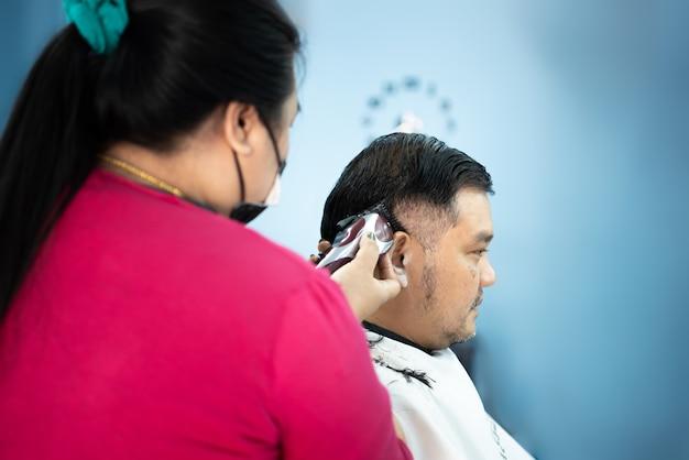 Niezidentyfikowany azjatycki fryzjer lub fryzurę strzyżenie klienta pulchnego ciała w modzie fryzurę w salonie fryzjerskim