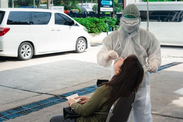 Niezidentyfikowany lekarz w kombinezonie ppe i badanie pacjenta azjatyckiego mężczyzny za pomocą próbki covid-19 wykonującej wymaz z jamy nosowo-gardłowej lub jamy ustnej i gardła w szpitalu