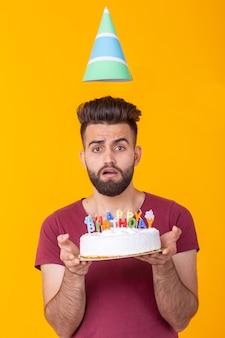 Niezidentyfikowany młody mężczyzna hipster z brodą trzymający tort z napisem gratulacje urodzinowe z okazji rocznicy i święta. koncepcja promocji i zniżek