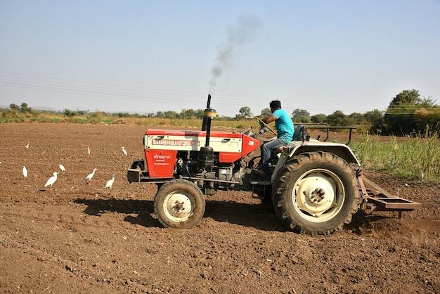 Niezidentyfikowany rolnik w ciągniku przygotowujący ziemię do siewu z kultywatorem przedsiewnym.