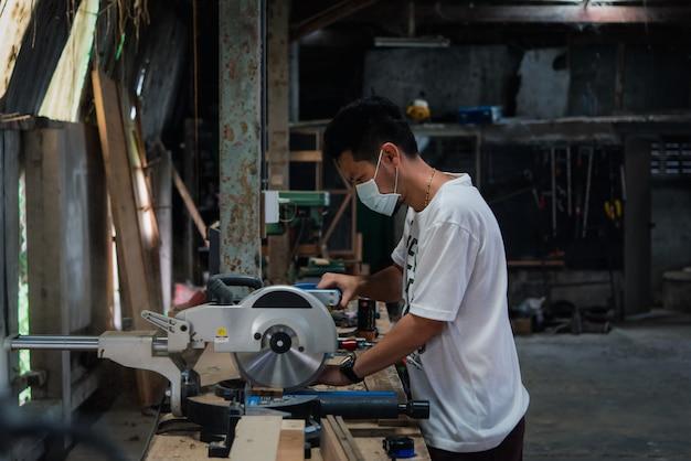 Niezidentyfikowany stolarz buduje meble lub produkty z listew i drewna z naturalnego drewna liściastego w magazynie lub tartaku w fabryce drewna w celu budowy lub sprzedaży