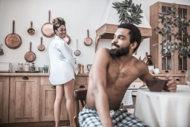 Niezła komunikacja. wesoła młoda kobieta ciemnoskóra gotowanie w kuchni obracając głowę patrząc męża jedzenie przy stole