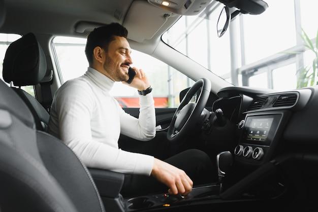 Niezła rozmowa biznesowa. przystojny młody biznesmen rozmawia przez swój inteligentny telefon i uśmiecha się siedząc na przednim siedzeniu
