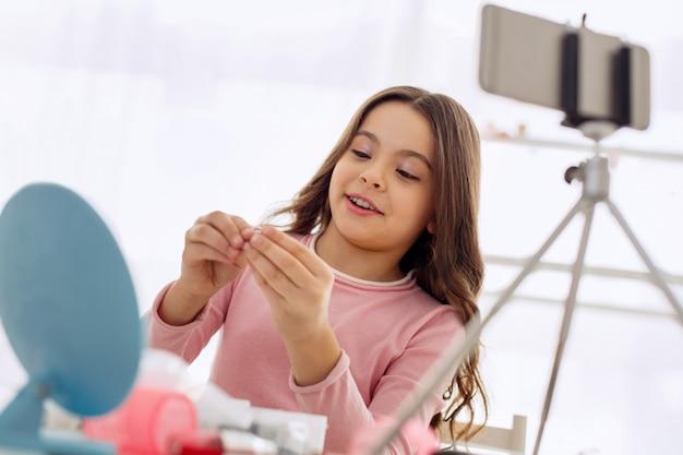 Niezła wskazówka. piękna nastolatka przeglądająca opaski do włosów na swoim vlogu o urodzie i dzieląca się wskazówkami podczas nagrywania siebie na blogu poświęconym urodzie