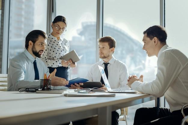 Niezłe wyjaśnienia. uroczy młody szef objaśnia kolegom nową koncepcję projektu podczas spotkania z nimi w swoim biurze