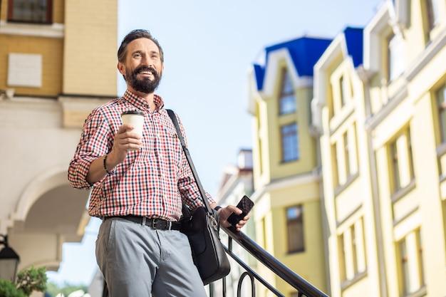 Niezły początek. radosny brodaty mężczyzna trzyma kawę idąc do pracy