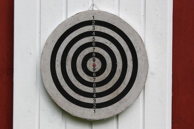 Nieznaczny strzał zbliżenie tarczy powieszony na białej i czerwonej ścianie
