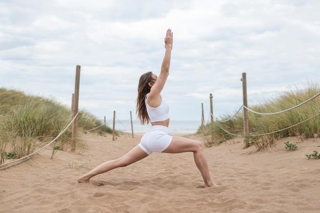 Nieznana blond kaukaska kobieta uprawiająca jogę na plaży ubrana w białą odzież sportową, która jest przeciw wybrzeżowi