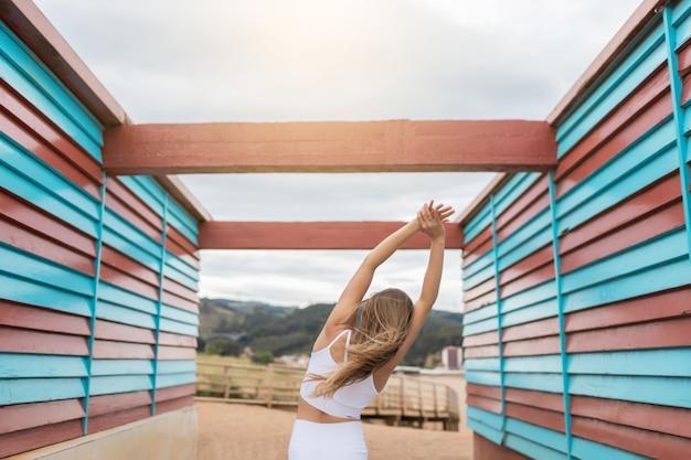 Nieznana blondynka uprawiająca jogę na świeżym powietrzu z białą odzieżą sportową między czerwoną i niebieską drewnianą kabiną