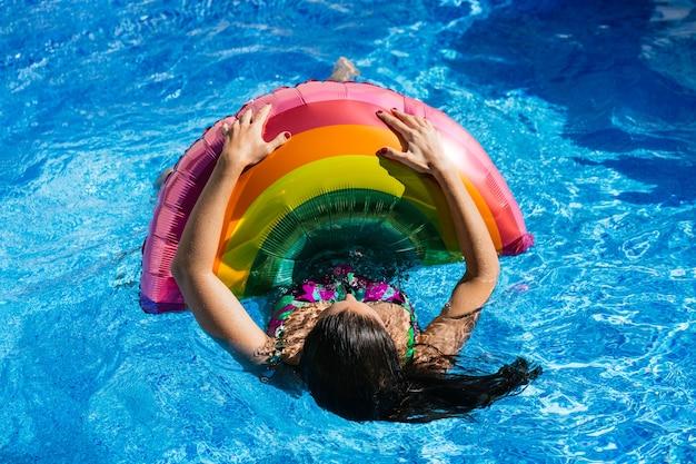 Nieznana brunetka unosząca się na falistej wodzie basenu, trzymająca się tęczowego balonu. koncepcja lata i lgbti.