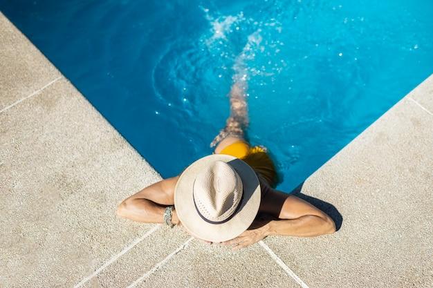 Nieznana kobieta w basenie. opala się w basenie. ubrana jest w żółty strój kąpielowy i kapelusz.
