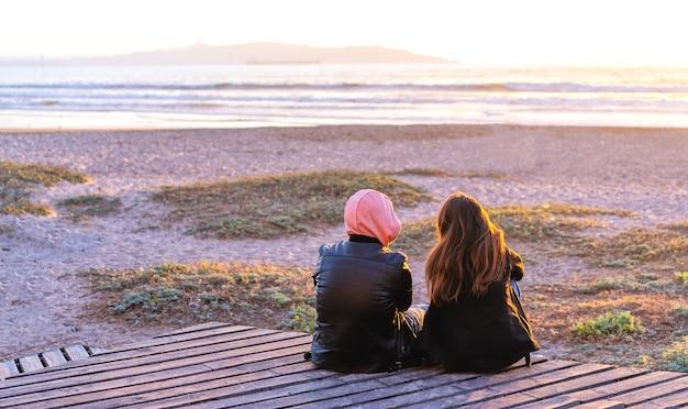 Nieznana młoda para siedzi, ogląda lub rozmawia na pokładzie na plaży o zachodzie słońca