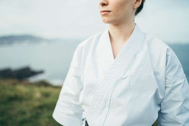 Nieznana młoda zawodniczka karate odwracająca wzrok na szczycie klifu