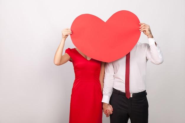 Nieznana para chowa się za wielkim czerwonym sercem. wewnątrz, studio strzał, na białym tle na szarym tle