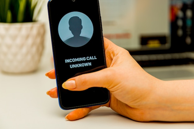 Nieznany rozmówca. mężczyzna trzyma telefon w dłoni i myśli o zakończeniu rozmowy. przychodzące z nieznanego numeru. incognito lub anonimowe