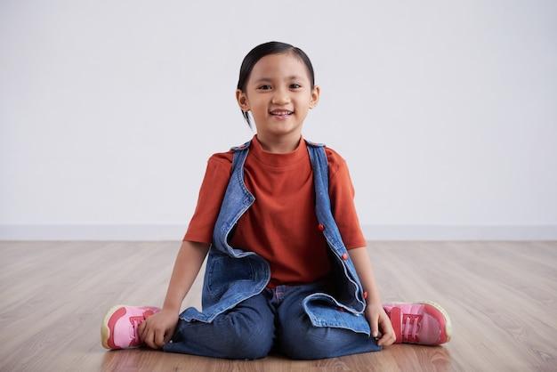 Niezobowiązująco ubierający azjatycki dziewczyny obsiadanie na kolanach na drewnianej podłoga w studiu