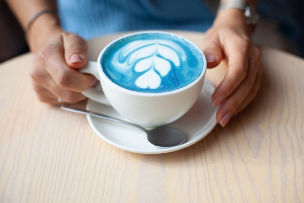Niezogniskowana kobieta ręce trzymając kubek gorącej motylkowej latte grochu lub niebieskiej spiruliny latte na drewnianym stole. organiczny zdrowy i modny napój. koncepcja dobrego samopoczucia i detoksykacji. skopiuj miejsce.