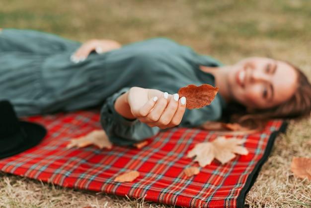 Niezogniskowana kobieta trzyma liście na koc piknikowy