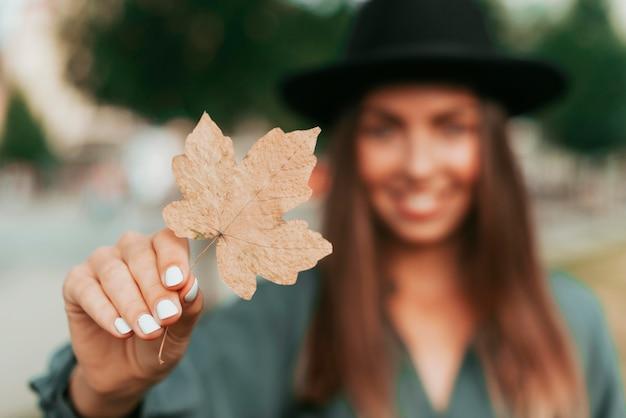 Niezogniskowana młoda kobieta w czarnym kapeluszu, trzymając liść
