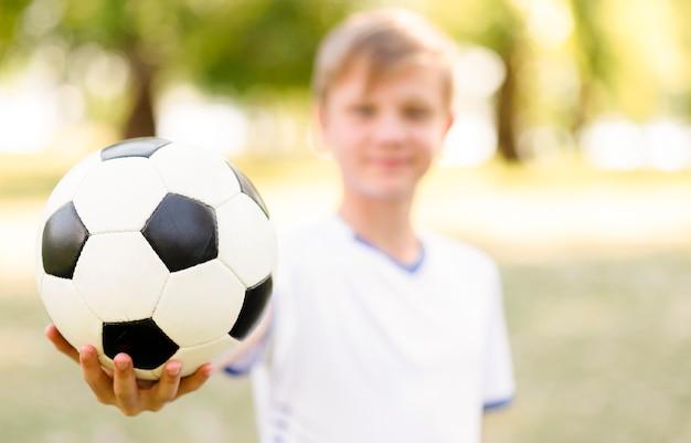 Niezogniskowany blond chłopiec trzymający piłkę nożną