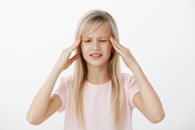 Niezorientowany, zmartwiony dzieciak nie może jasno myśleć i zapamiętywać informacji. zaniepokojona zdezorientowana młoda dziewczyna o blond włosach, trzymająca się za skronie i krzywiąca się, próbująca coś sobie przypomnieć