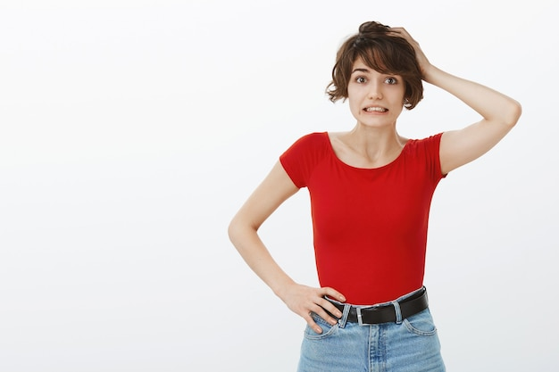 Niezręczna głupia kobieta drapiąca się po głowie i wyglądająca na zdezorientowaną