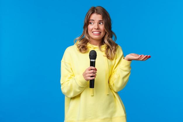 Niezręczna śliczna blond dziewczyna nie zna tekstów śpiewających karaoke, patrzy na nerwowy uśmiech przyjaciela, zawstydzona śpiewa przed ludźmi, trzyma mikrofon, stoi niebieską ścianę