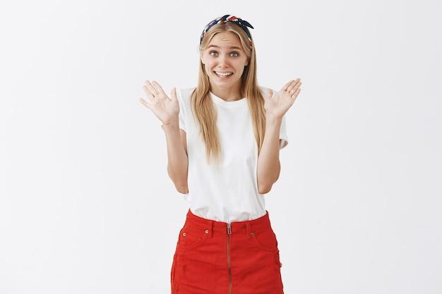 Niezręczna śliczna blond dziewczyna pozuje pod białą ścianą