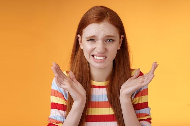 Niezręcznie, nieszczęśliwa, zmartwiona młoda rudowłosa dziewczyna kuli się, przepraszam, uśmiechając się, uśmiechając się nerwowo, marszcząc brwi, mrużąc oczy, rozłożone w bok, wzruszając zdezorientowanymi, stojąc na pomarańczowym tle.