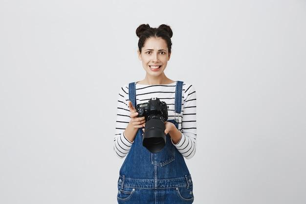 Niezręcznie uśmiechnięta dziewczyna trzyma aparat, robi zdjęcia