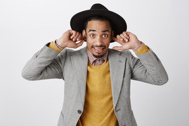Niezręczny afroamerykanin zatknął uszy i wyglądał na zdezorientowanego, nic nie słyszy w głośnym miejscu