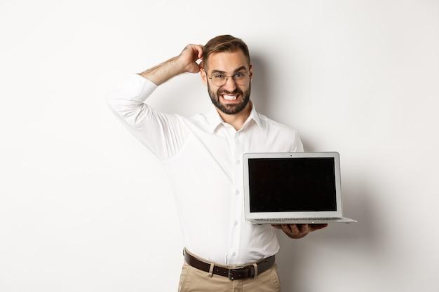 Niezręczny biznesmen pokazuje ekran laptopa i wygląda niepewnie, stojąc niewygodnie na białym tle.