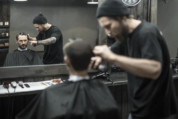 Niezrównany fryzjer z brodą i tatuażem obcina włosy brodatemu klientowi w salonie fryzjerskim