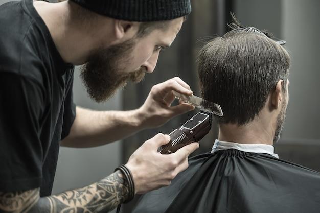 Niezrównany fryzjer z brodą i tatuażem obcina włosy swojej klientce w czarnej pelerynie w zakładzie fryzjerskim
