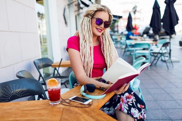 Niezwykła blondynka z dredami siedzi w kawiarni na ulicy, trzymając notes, ciesząc się wolnym czasem. nosi jasne spodnie z tropikalnym nadrukiem.