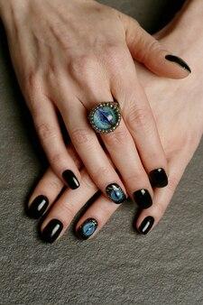 Niezwykła fantazja zdobienia paznokci i pierścień na wypielęgnowanych rękach z bliska