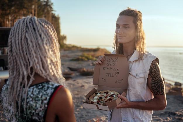 Niezwykła propozycja. śliczny blondyn składający niezwykłą propozycję swojej kobiecie trzymającej pudełko z pizzą