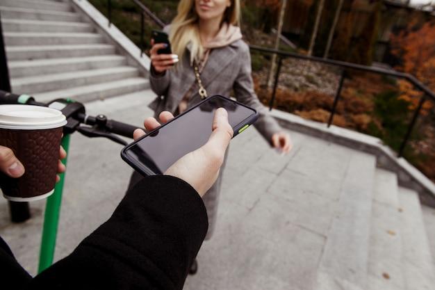 Niezwykła romantyczna randka na skuterach elektrycznych. widok pierwszoosobowy. mężczyzna trzyma smartfon z pustym ekranem przestrzeni kopii, filiżanką kawy i kołem. kobieta stojąca w pobliżu z telefonem w dłoni i uśmiechnięta.