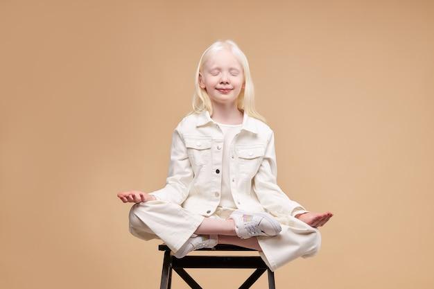 Niezwykłe dziecko albinos obcych siedzieć w pozie jogi na białym tle