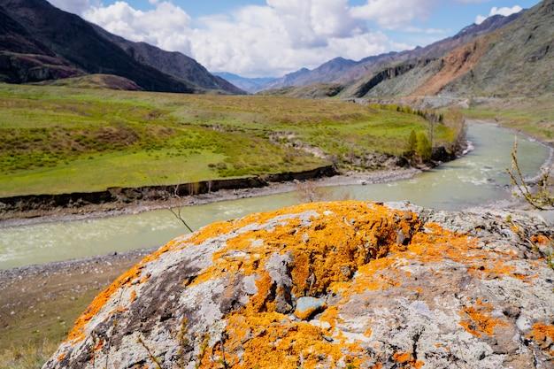 Niezwykłe formacje kamienne z kolorowymi łatami porostów i mchu na tle gór i rzeki