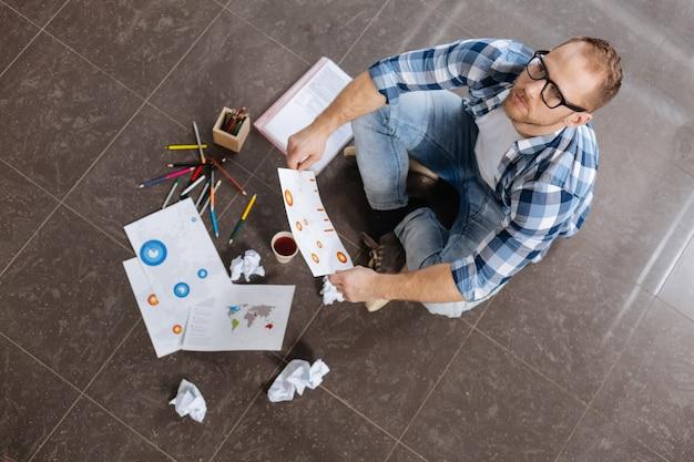 Niezwykłe miejsce pracy. poważny inteligentny przystojny mężczyzna siedzi na podłodze i trzymając swój rysunek, myśląc o swoim nowym projekcie